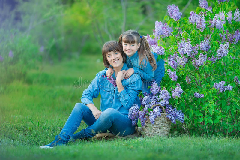 Cute adorable beautifull mother lady mom woman with brunette girl daughter in meadow of lilac purple bush.People in jeans wear. royalty free stock image