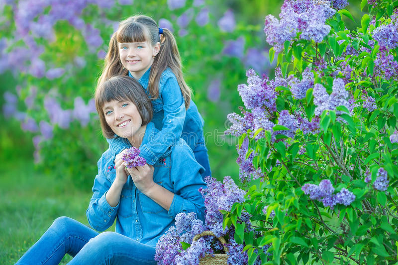 Cute adorable beautifull mother lady mom woman with brunette girl daughter in meadow of lilac purple bush.People in jeans wear. royalty free stock photo