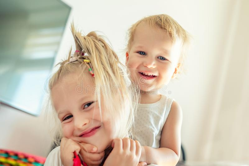 Cute adorable blond caucaian little sister hugging her toddler brother.couple of cheerful sibling playing indoor. Cute girl and stock image