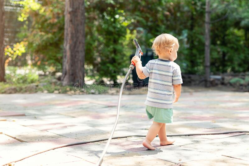 Cute adorable caucasian blond barefeet boy walking at home backyard holding hose pipe for watering garden. Child little royalty free stock image