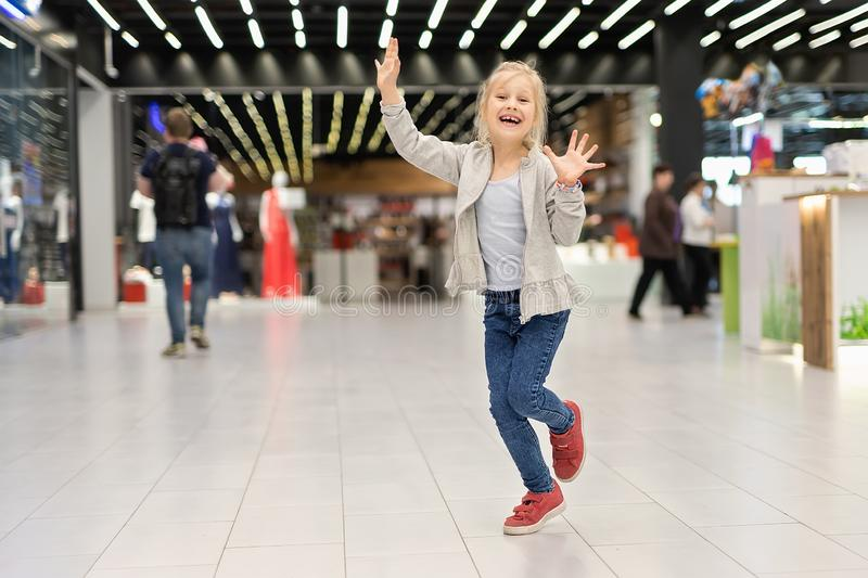 Cute adorable caucasian blond girl enjoy walking at shopping mall. Beautiful cheerful child having fun and running at retail royalty free stock photography