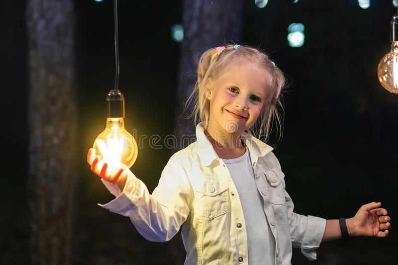 Cute adorable caucasian blond girl portrait smiling and holding in hand one of hanged edison light bulb at forest outdoor. Right royalty free stock images