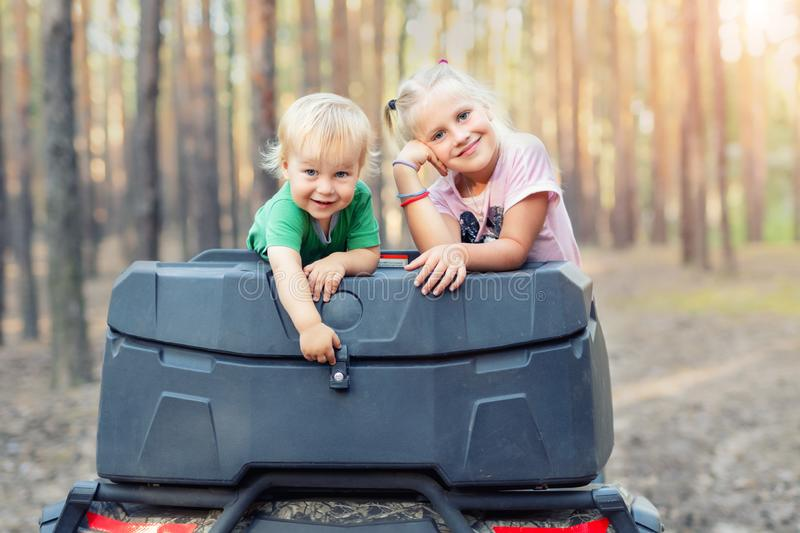 Cute adorable caucasian blond siblings having fun during atv 4x4 off-road adventure trip amog coniferous pine forest on brigh. Sunny day. Little boy and girl stock photos