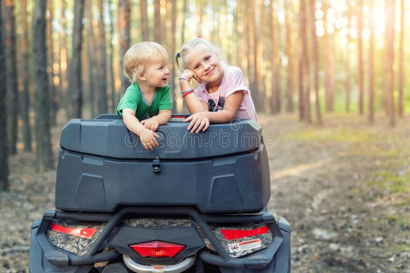 Cute adorable caucasian blond siblings having fun during atv 4x4 off-road adventure trip amog coniferous pine forest on brigh. Sunny day. Little boy and girl stock photo