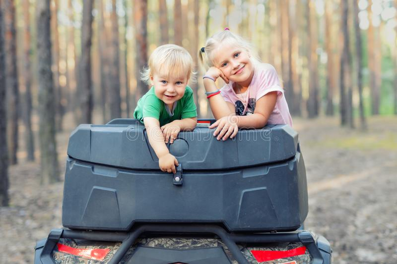 Cute adorable caucasian blond siblings having fun during atv 4x4 off-road adventure trip amog coniferous pine forest on brigh. Sunny day. Little boy and girl royalty free stock photography