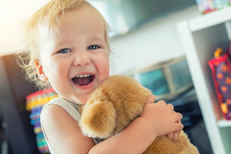 Cute adorable caucasian blond toddler boy having fun, laughing and hugging soft puppy toy indoors. Cheerful child playing with royalty free stock images