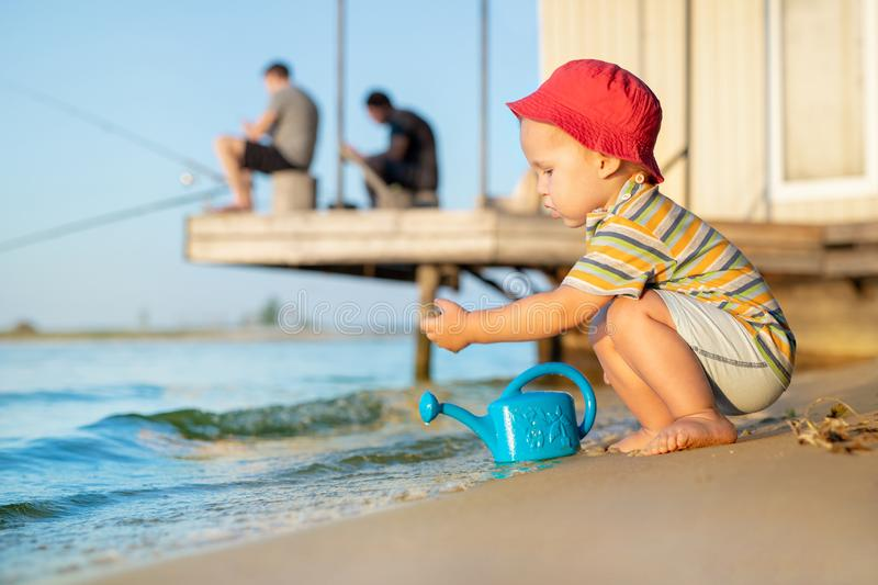 Cute adorable caucasian blond toddler boy having fun playing with blue watering can at river or lake sandy shore while father. Fishing on background. Child stock photos