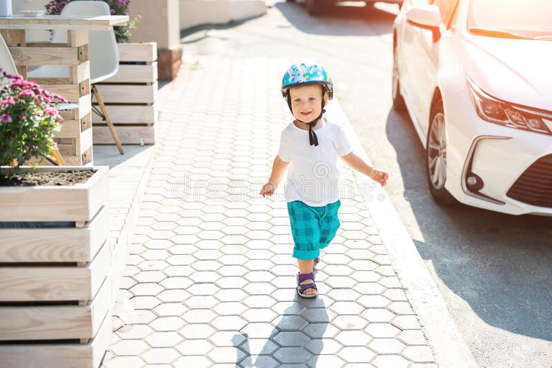 Cute adorable caucasian blond toddler boy in helmet walking at city street going to ride bicycle ot scooter on bright stock images