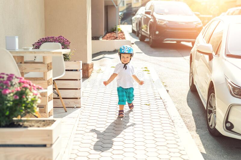 Cute adorable caucasian blond toddler boy in helmet walking at city street going to ride bicycle ot scooter on bright royalty free stock photos