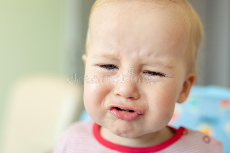 Cute adorable caucasian blond toddler boy sitting in high chair and crying while feeding. Upset unhappy child refuse to eat. Healthy diet food and demanding bad stock photos