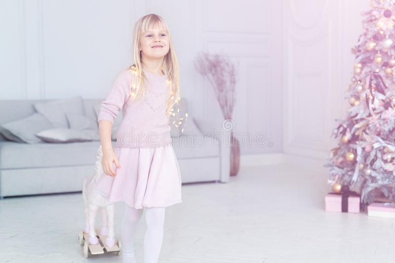 Cute adorable caucasian little blond smiling girl portrait enjoy playing rocking horse near christmas tree at home indoors. Happy. Child looking and dreaming royalty free stock photography