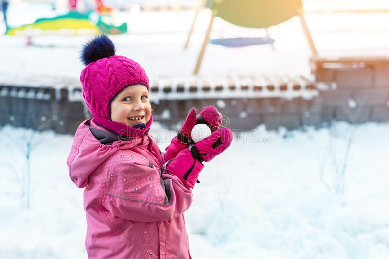 Cute adorable caucasian little girl winter portrait holding snowball in hands ready for snow fight at playground outdoor. Funny. Playful child during snowfall stock images