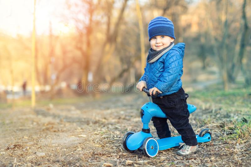 Cute adorable caucasian toddler boy in blue jacket having fun riding three-wheeled balance run bike scooter in city park or forest stock images