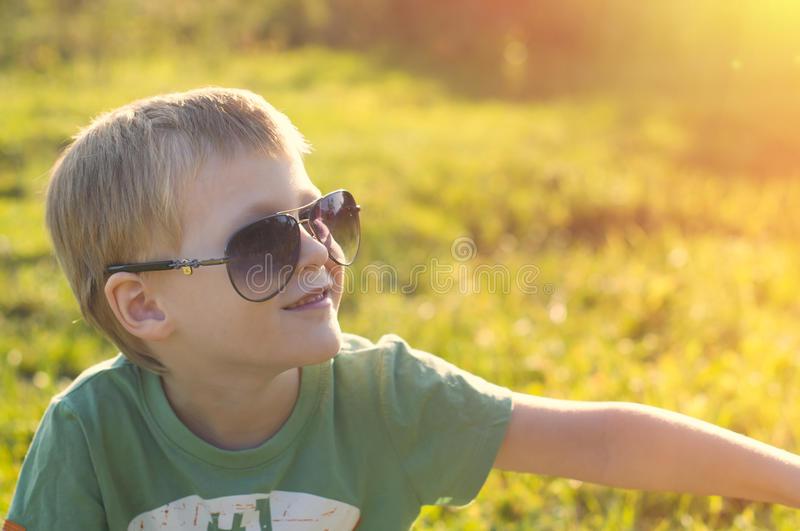 Cute adorable child in sunglasses sitting on green grass in the stock photo