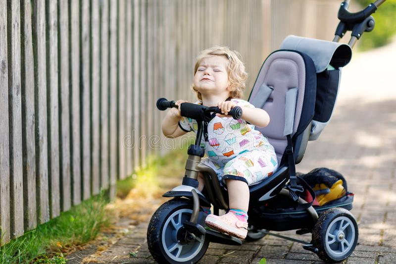 Cute adorable crying sad toddler girl sitting on pushing bicyle or tricycle. Little baby child going for a walk with stock image