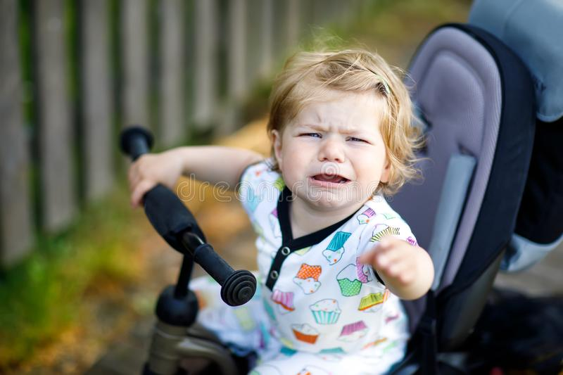 Cute adorable crying sad toddler girl sitting on pushing bicyle or tricycle. Little baby child going for a walk with stock photos
