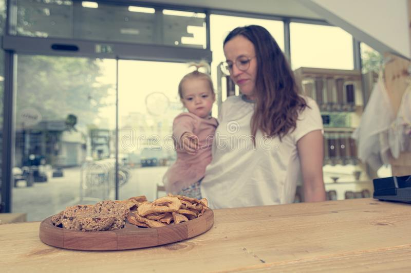 Cute adorable girl trying cookies at organic store with her mother. royalty free stock images