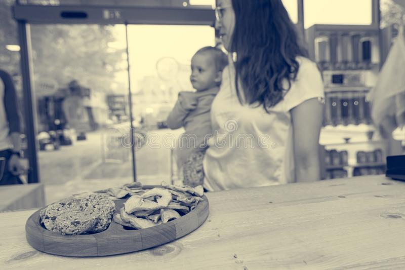 Cute adorable girl trying cookies at organic store with her mother. stock photos