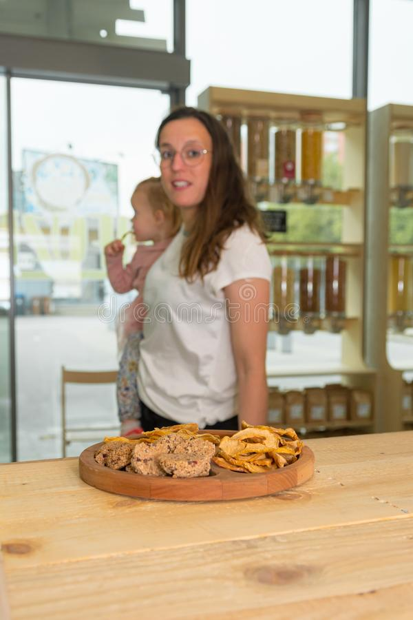 Cute adorable girl trying cookies at organic store with her mother. stock image