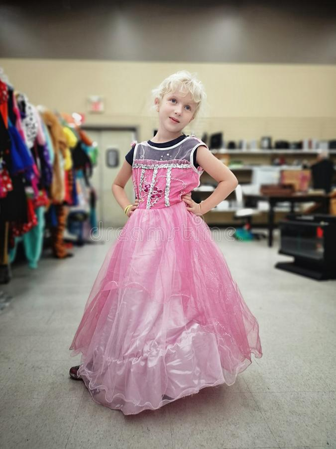 Cute adorable girl trying on costume pink fairy dress in store for Halloween holiday celebration stock image