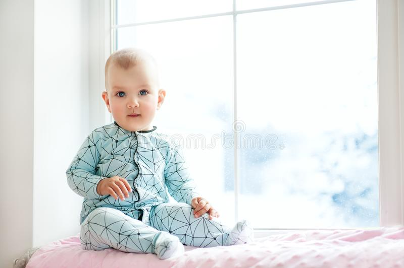 Cute adorable little baby girl sitting by window and looking to cam. Kid enjoy snowfall. Happy holidays and Christmas! Winter Home royalty free stock image