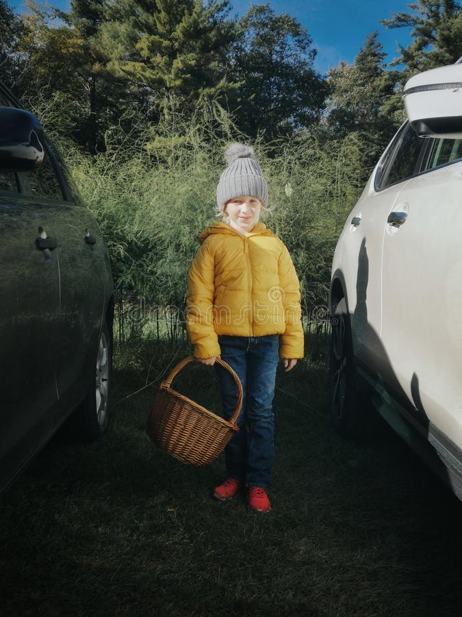 cute adorable little Caucasian girl in yellow jacket and warm grey hat. Child on farm with wicker basket going to pick fresh apple royalty free stock images