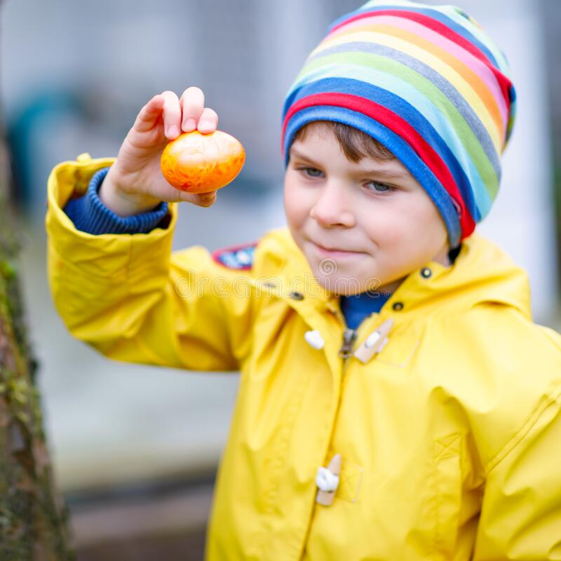Cute adorable little kid boy making an egg hunt on Easter. Happy child searching and finding colorful eggs in domestic royalty free stock photography