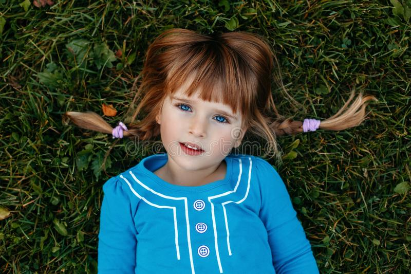 Cute adorable little red-haired Caucasian girl child in blue dress lying in field meadow park outside. Closeup portrait of cute adorable little red-haired stock photo