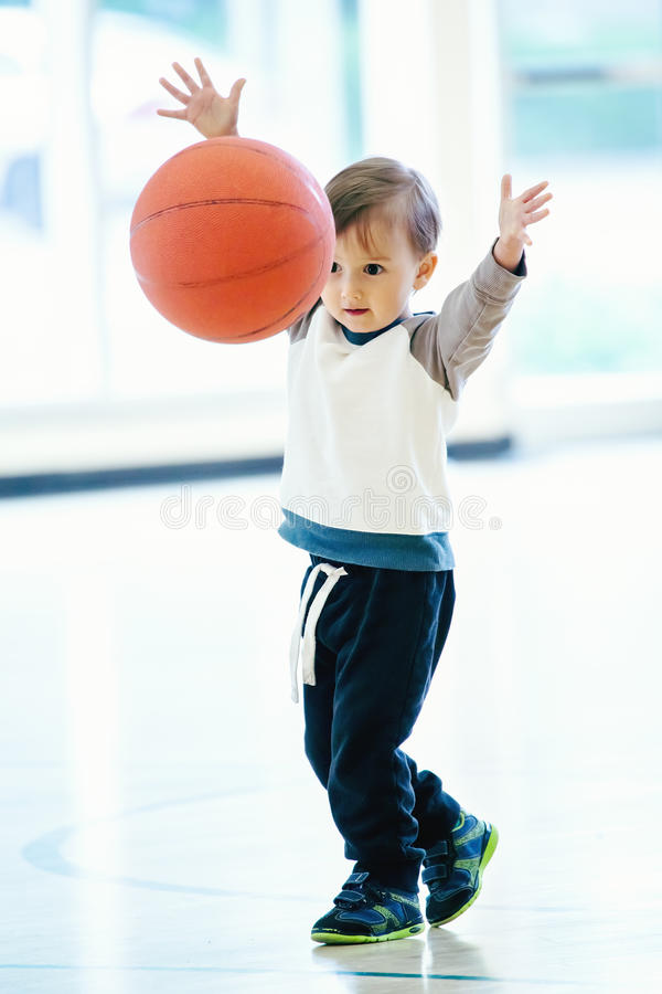 Cute adorable little small white Caucasian child toddler boy playing with ball in gym. Having fun, healthy lifestyle childhood concept royalty free stock photo