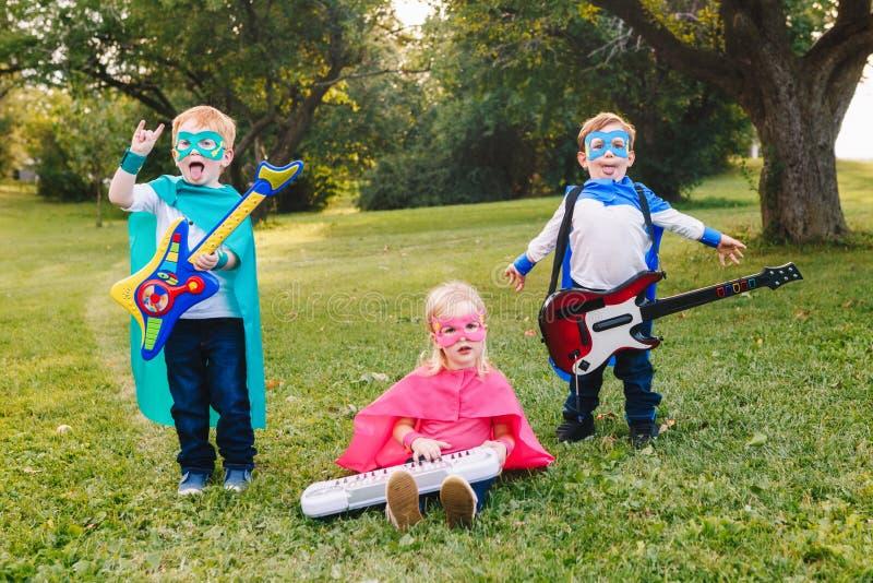 Preschool Caucasian children playing superheroes. Cute adorable preschool Caucasian children playing superheroes music band rock group. Three kids friends having stock photos