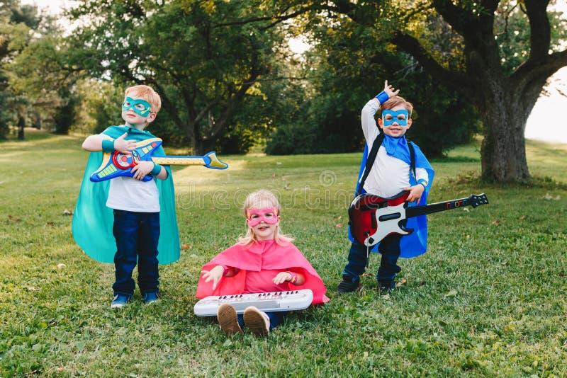 Preschool Caucasian children playing superheroes. Cute adorable preschool Caucasian children playing superheroes music band rock group. Three kids friends having royalty free stock photography