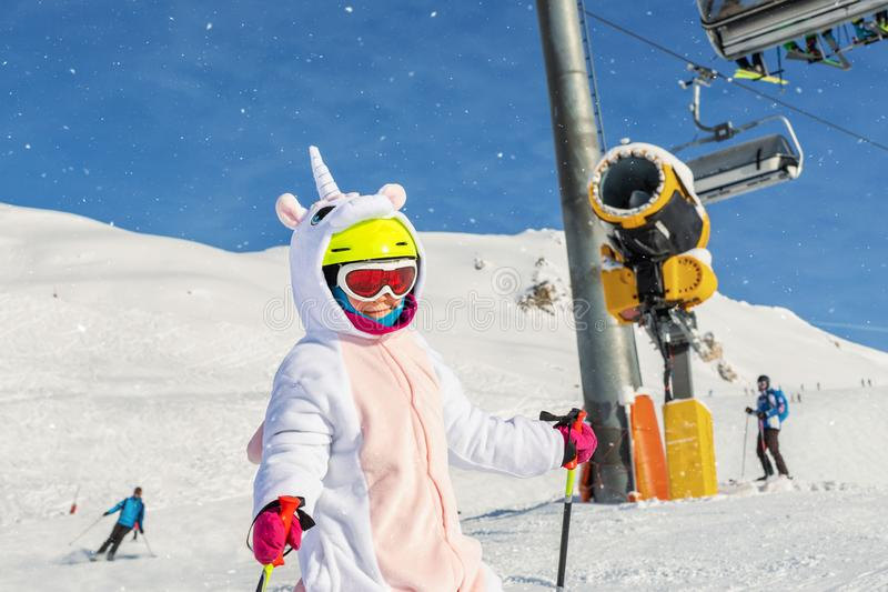 Cute adorable preschooler caucasian kid girl portrait with ski in helmet, goggles and unicorn fun costume enjoy winter royalty free stock photos