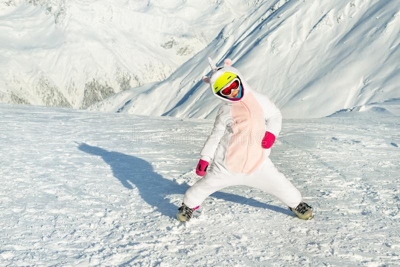 Cute adorable preschooler caucasian kid girl portrait with ski in helmet, goggles and unicorn fun costume enjoy winter royalty free stock photography