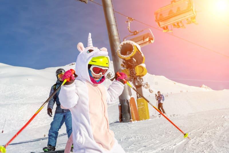 Cute adorable preschooler caucasian kid girl portrait with ski in helmet, goggles and unicorn fun costume enjoy winter stock images