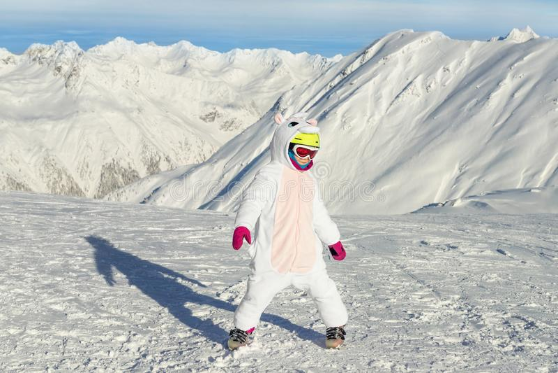 Cute adorable preschooler caucasian kid girl portrait with ski in helmet, goggles and unicorn fun costume enjoy winter stock photos