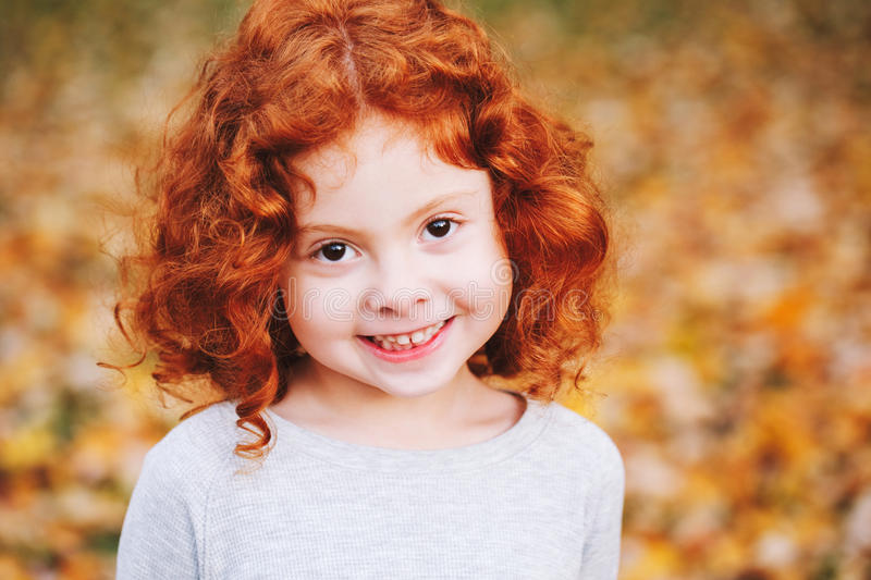 Cute adorable smiling little red-haired Caucasian girl child standing in autumn fall park outside, looking away. Closeup portrait of cute adorable smiling little royalty free stock photography