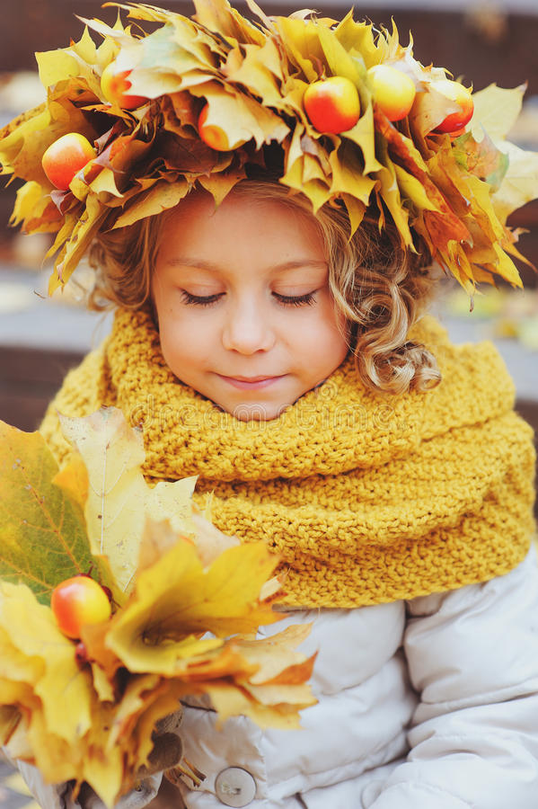 Cute adorable toddler girl portrait with bouquet of autumn leaves and wreath walking outdoor in park royalty free stock photo