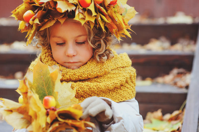 Cute adorable toddler girl portrait with bouquet of autumn leaves and wreath walking outdoor in park royalty free stock photos