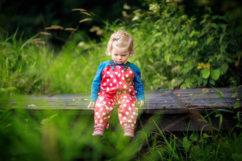 Cute adorable toddler girl sitting on wooden bridge and throwing small stones into a creek. Funny baby having fun with. Outdoor games in nature stock photo