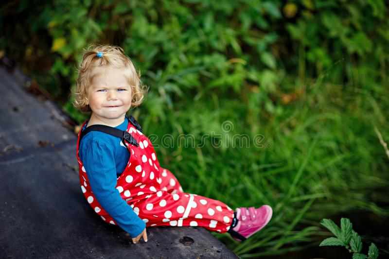 Cute adorable toddler girl sitting on wooden bridge and throwing small stones into a creek. Funny baby having fun with royalty free stock image