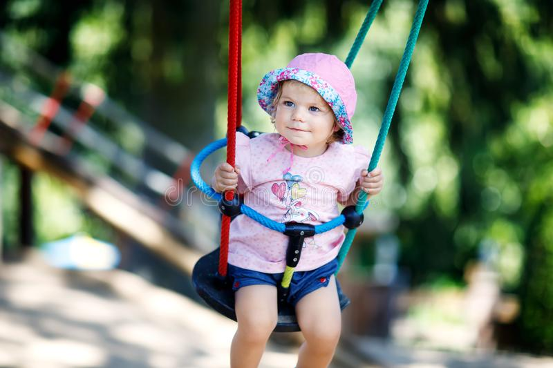 Cute adorable toddler girl swinging on outdoor playground. Happy smiling baby child sitting in chain swing. Active baby stock image
