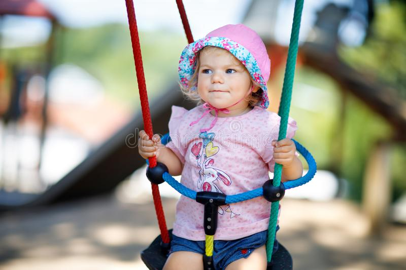 Cute adorable toddler girl swinging on outdoor playground. Happy smiling baby child sitting in chain swing. Active baby royalty free stock photo