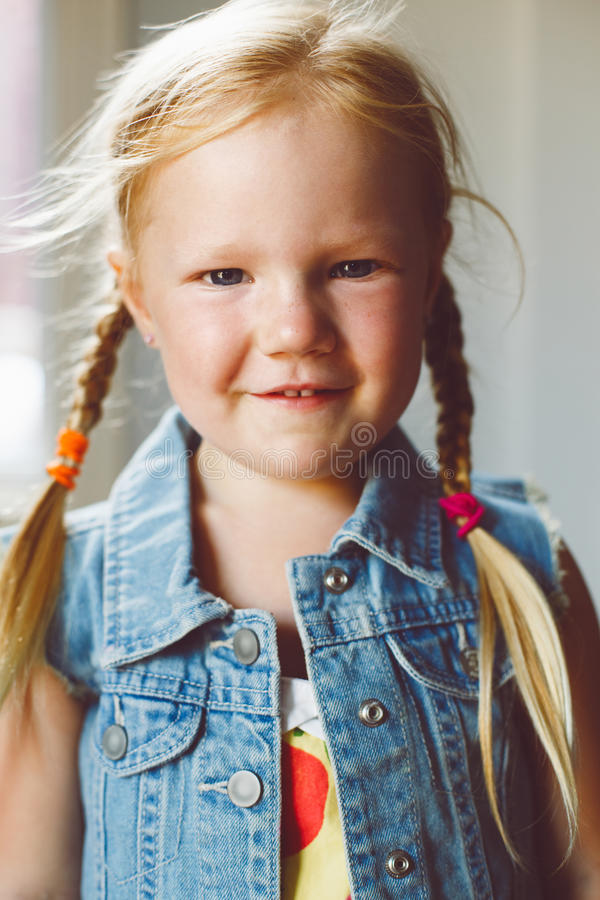Cute adorable white blonde Caucasian smiling girl looking in camera. Closeup portrait of cute adorable white blonde Caucasian smiling girl looking in camera royalty free stock images
