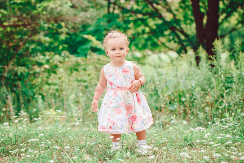 Cute adorable white Caucasian baby girl child in white dress standing in green summer park forest outside royalty free stock photo
