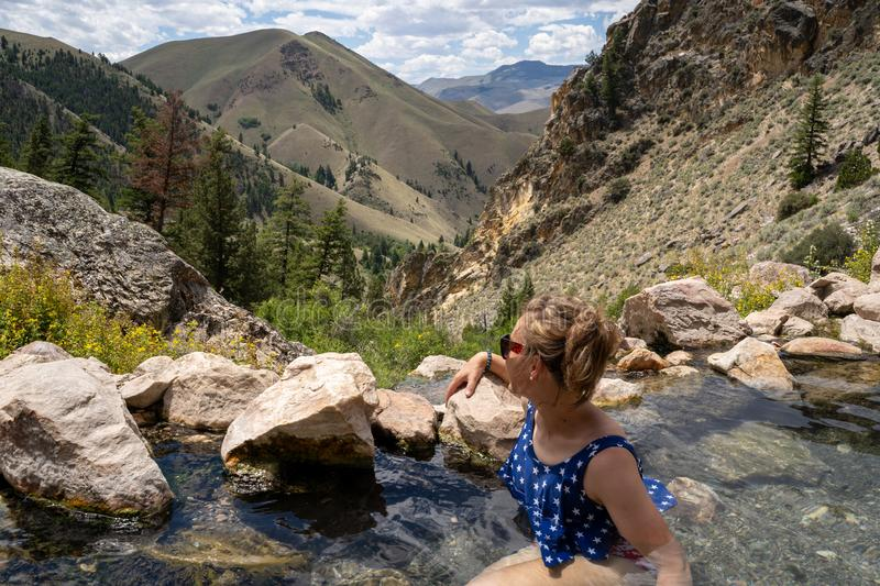Cute adult woman wearing an American flag swimsut soaks and enjoys the Goldbug Hot Springs in the Salmon Challis National Forest. Of Idaho royalty free stock photo