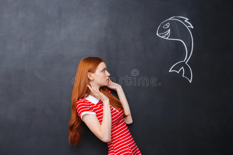 Cute afraid woman scared of shark drawn on chalkboard background. Cute redhead afraid young woman scared of small shark drawn on chalkboard background royalty free stock images