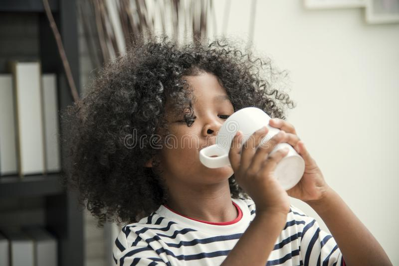 Cute African American boy drinking water from mug. royalty free stock photos