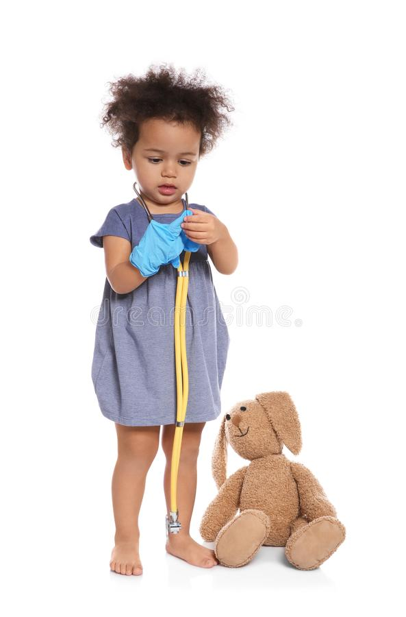 Cute African American child imagining herself as doctor while playing with stethoscope and toy bunny on white stock image