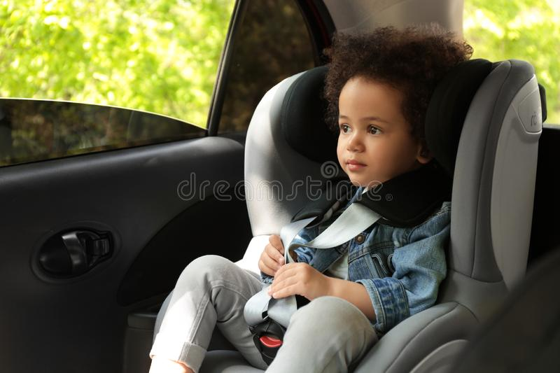 Cute African-American child sitting in safety seat inside car royalty free stock photo