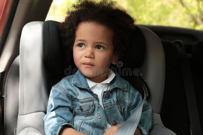Cute African-American child sitting in safety seat. Danger prevention stock photography